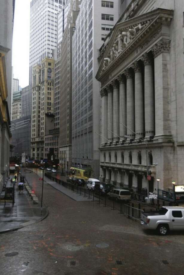 Rain falls outside the New York Stock Exchange, right, usually crowded with tourists, in New York on Saturday, Aug. 27, 2011 ahead of Hurricane Irene. (AP Photo/Mary Altaffer)