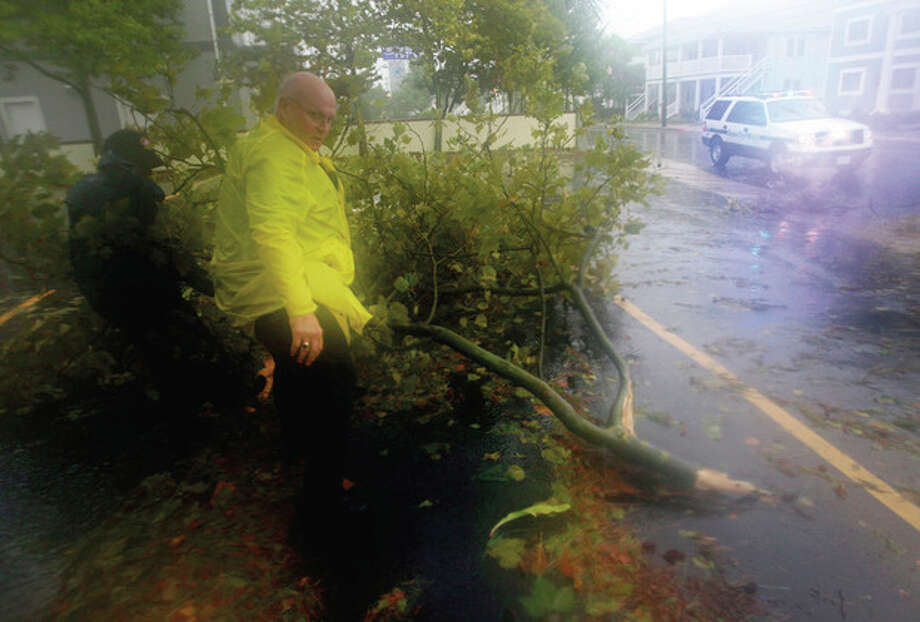 Members of the Ocean City Police Department clear a fallen tree branch from a street in Ocean City, Md., Saturday, Aug. 27, 2011, as Hurricane Irene heads toward the Maryland coast. Hurricane Irene knocked out power and piers in North Carolina, clobbered Virginia with wind and churned up the coast Saturday to confront cities more accustomed to snowstorms than tropical storms. (AP Photo/Patrick Semansky) / AP