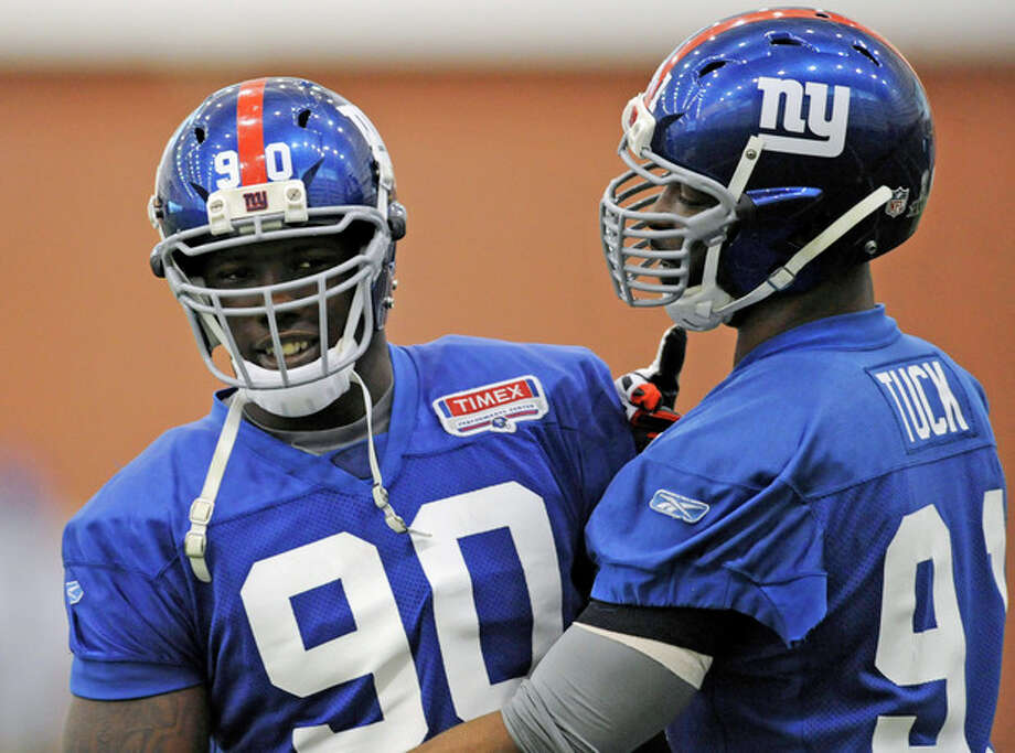 New York Giants defensive ends Jason Pierre-Paul, left, and Justin Tuck meet during NFL football practice on Friday, Jan. 27, 2012, in East Rutherford, N.J. The Giants are scheduled to face the New England Patriots in Super Bowl XLVI on Feb. 5 in Indianapolis. (AP Photo/Bill Kostroun) / FR51951 AP