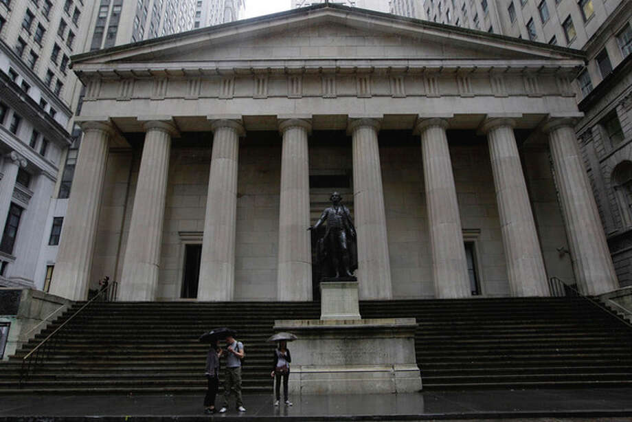 Visitors to the usually crowded Wall St. area stand in front Federal Hall in the financial district of New York on Saturday, Aug. 27, 2011 ahead of Hurricane Irene. (AP Photo/Mary Altaffer) / AP