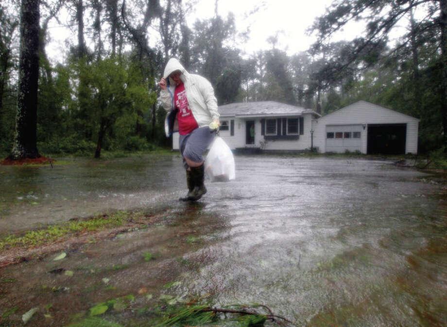 Joanna Southaid, removes belongs from her home as flood waters rise in New Bern, N.C., Saturday, Aug. 27, 2011 as Hurricane Irene hits the North Carolina coast. (AP Photo/Chuck Burton) / AP