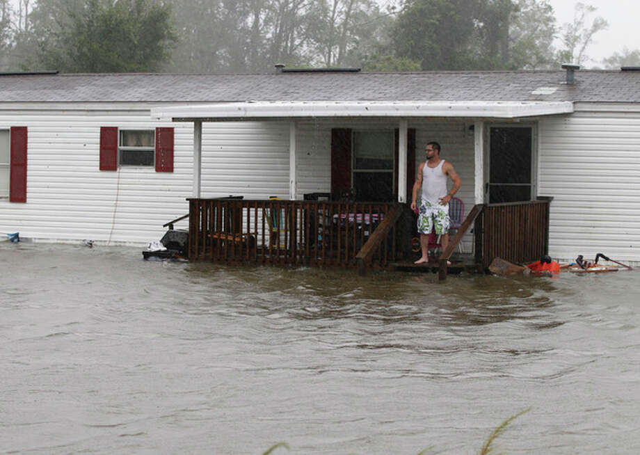 Jarod Wilton looks at the flood waters rising to his doorstep, Saturday, Aug. 27, 2011, in Alliance, N.C., as Hurricane Irene hits the North Carolina coast. (AP Photo/Chuck Burton) / Copyright 2011 The Associated Press. All rights reserved. This material may not be published, broadcast, rewritten or redistributed.