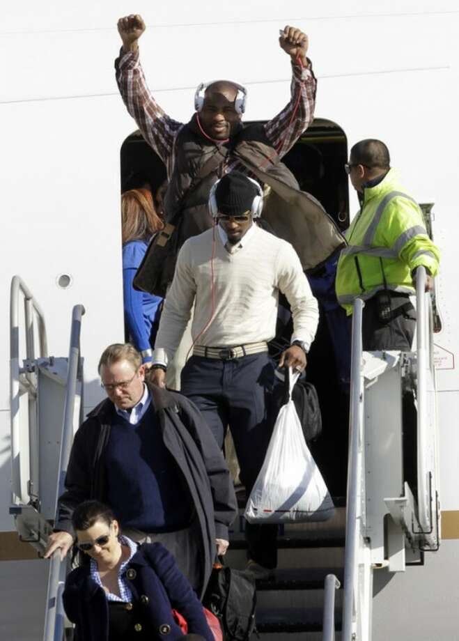 New York Giants running back Brandon Jacobs, top, raises his hands as he arrives with his NFL football team at Newark Liberty International Airport, Monday, Feb. 6, 2012, in Newark, N.J. A day earlier, the Giants beat the New England Patriots in Super Bowl XLVI. (AP Photo/Julio Cortez)