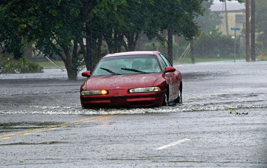 A man drives his car through a flooded street in New Bern, N.C., Saturday, Aug. 27, 2011 as Hurricane Irene hits the North Carolina coast. Hurricane Irene knocked out power and piers in North Carolina, clobbered Virginia with wind and churned up the coast Saturday to confront cities more accustomed to snowstorms than tropical storms. (AP Photo/Chuck Burton) / AP