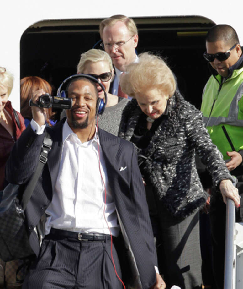 New York Giants outside linebacker Michael Boley, left, holds a video camera as he arrives with members of New York Giants NFL football team, including owner John Mara, center back, and his mother Ann Mara, right, at Newark Liberty International Airport, Monday, Feb. 6, 2012, in Newark, N.J. A day earlier, the Giants beat the New England Patriots in Super Bowl XLVI. (AP Photo/Julio Cortez) / AP