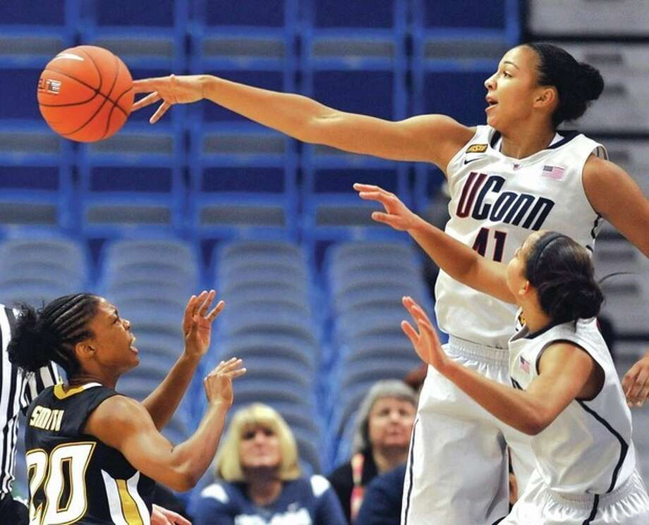 AP photo UConn's Kiah Stokes, top right, blocks a shot by Towson's Markell Smith, left, as Connecticut's Bria Hartley, bottom right, watches during Wednesday night's game. UConn routed Towson, 92-31. / AP2011