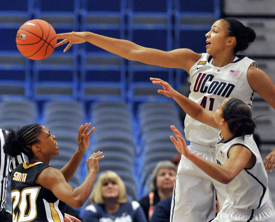 Connecticut's Kiah Stokes, top right, blocks a shot by Towson's Markell Smith, left, as Connecticut's Bria Hartley, bottom right, defends in the first half of an NCAA college basketball game in Hartford, Conn., Wednesday, Nov. 30, 2011. (AP Photo/Jessica Hill) / AP2011