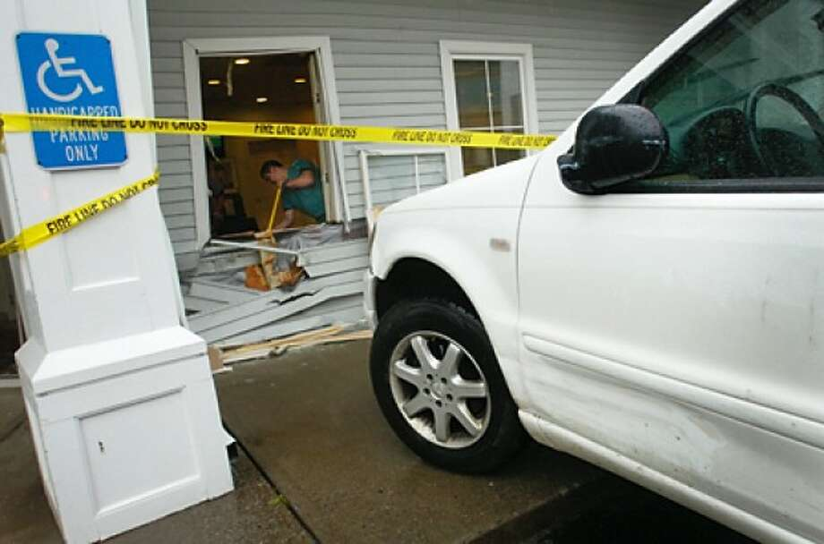 Employees of the Emergency Veterinary Clinic on West Cedar St clean up broken glass after the driver of a Mercedes SUV crashed through the front windows of the business Wednesday morning. Hour photo / Erik Trautmann