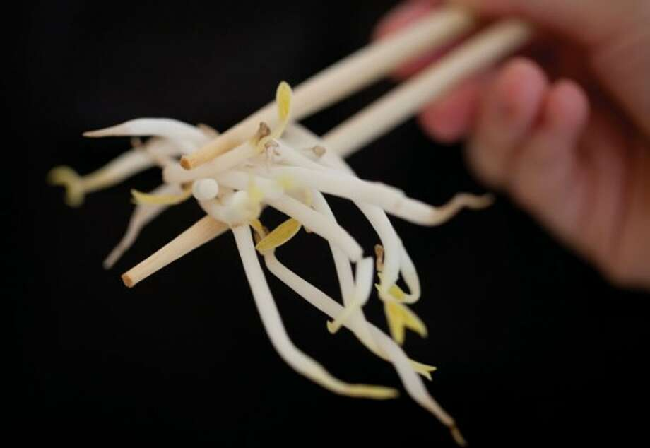 A woman holds bean sprouts with chopsticks in Berlin, Germany, Sunday, June 5, 2011. Health authorities say locally grown beansprouts in northern Germany have been identified as the likely cause of an outbreak of E. coli that has killed at least 22 people and sickened hundreds in Europe. (AP Photo/Gero Breloer)