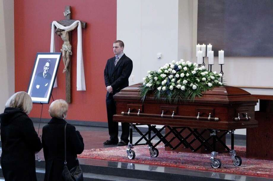 Two women pause to pay their respect in front of the casket of legendary Penn State football coach Joe Paterno during a public viewing in the Worship room of the Pasquerilla Spiritual Center on the Penn State University campus, Tuesday, Jan. 24, 2012 in State College, Pa. (AP Photo/Gene J. Puskar) / AP