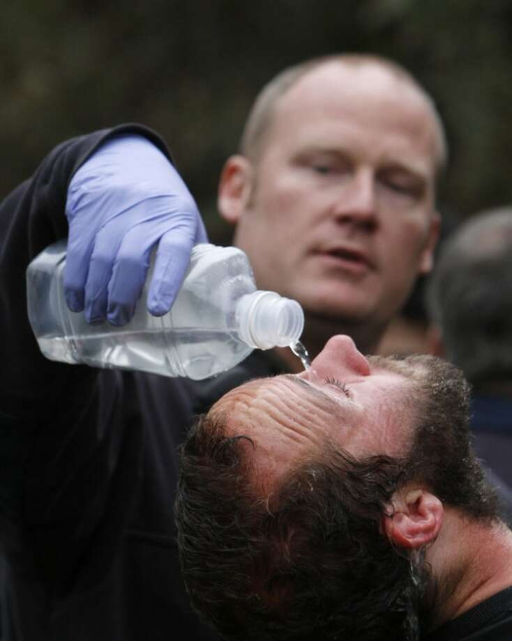 University of California, Davis, student Mike Fetterman, receives a treatment for pepper spray by UC Davis firefighter Nate Potter, after campus police dismantled an Occupy Wall Street encampment on the campus quad in Davis, Calif., Friday, Nov. 18, 2011. UC Davis officials say eight men and two women were taken into custody. (AP Photo/Rich Pedroncelli)