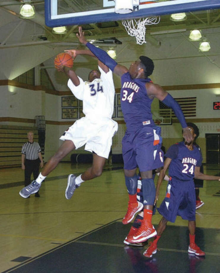 King's Guilbert Francois, left, tries to get off a shot as 6-foot-9 Sean Obi of Greens Farms Academy defends during Monday's game in Westport. The Dragons avenged an earlier loss to the visiting Vikings by claiming a 75-52 victory.@Cutline Byline:Hour Photo/ Alex vonKleydorff
