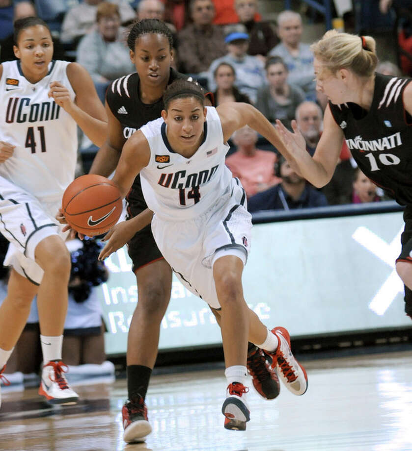 Connecticut's Bria Hartley brings the ball up while pursued by Cincinnati's Bjonee Reaves, second from left, in the first half of an NCAA college basketball game in Storrs, Conn., Thursday, Jan. 19, 2012. Connecticut's Kiah Stokes is at left, and Cincinnati's Kayla Cook is at right. (AP Photo/Bob Child) / FR170140 AP