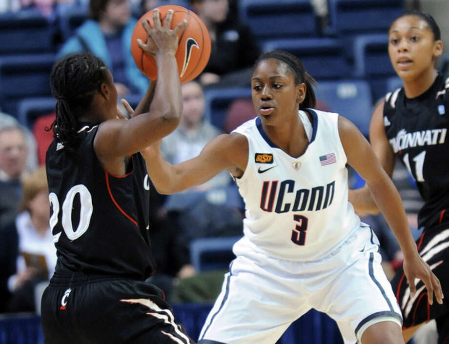 Cincinnati's Bjonee Reaves looks to pass the ball as Connecticut's Tiffany Hayes guards her in the first half of an NCAA college basketball game in Storrs, Conn., Thursday, Jan. 19, 2012. (AP Photo/Bob Child) / FR170140 AP