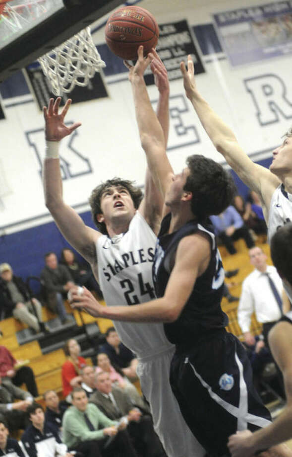 Hour photo/Matthew VinciRoss Whelan of Staples, left, goes up for a shot despite the defensive efforts of Wilton's Weston Wilbur. The Wreckers won Tuesday's game, 54-49.