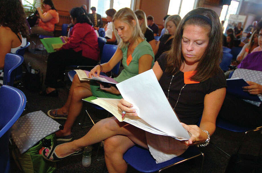 Hour photo / Alex von Kleydorff New teacher Patricia Conron looks over her informational packet before she starts as fourth-grade teacher at Rowayton Elementary School. / 2011 The Hour Newspapers