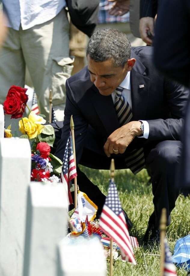 President Barack Obama place a challenge coin on the grave of a fallen soldier at Arlington National Cemetery on Memorial Day, Monday, May 30, 2011. (.(AP Photo/Jose Luis Magana)