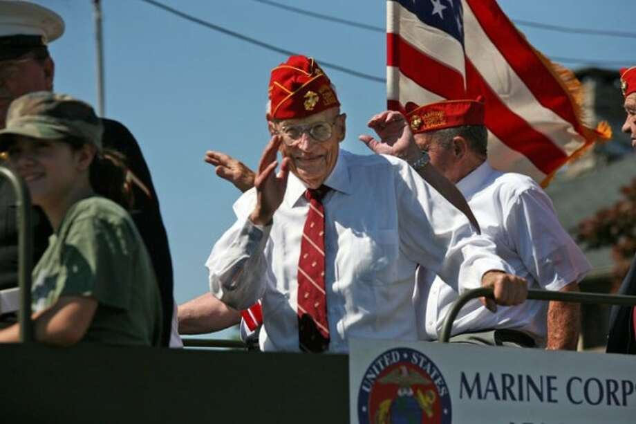 A Marine Corp Veteran waves to the crowd as he rides in Norwalk''s annual Memorial Day parade Monday morning. Hour Photo / Danielle Robinson