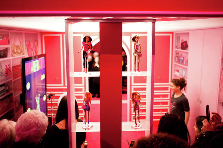 Barbie dolls stand on shelves at the Barbie Dream House party during Fashion Week in New York, Friday, Feb. 10, 2012. (AP Photo/John Minchillo) / AP