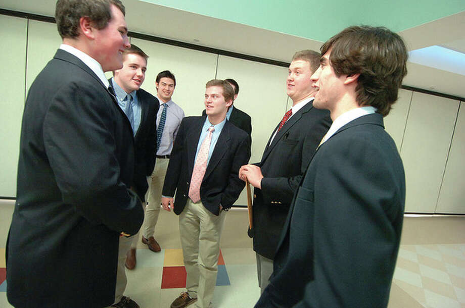 Hour Photo/Alex von KleydorffStaples football players, from left, Will Patrick, Kevin Kearney, Pieter Hoets, Joey Zelkowitz, Nick Kelly (obscured), Kyle Vaughn and James Frusciante gather together after announcing their college plans at a ceremony at the high school in Westport. / 2013 The Hour Newspapers