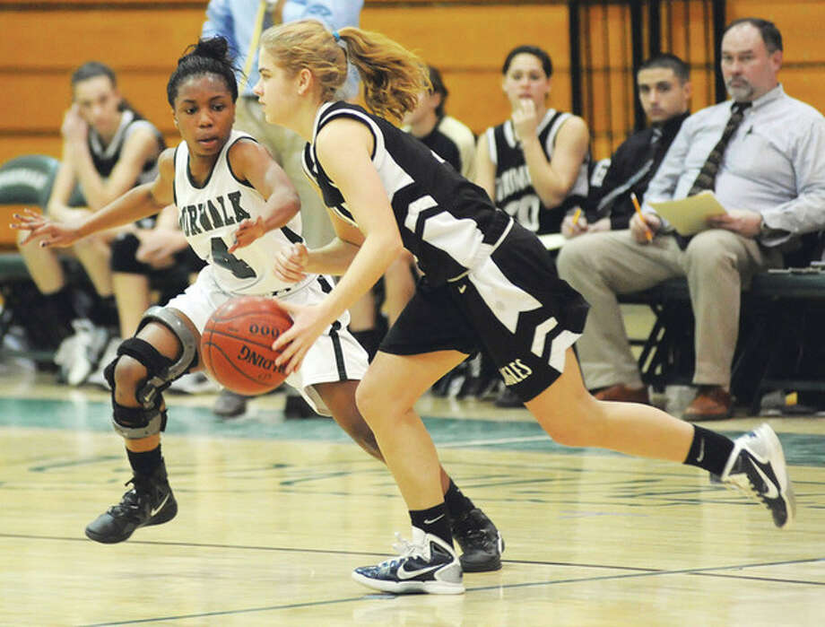 Hour photo/John Nash Norwalk guard Zayna Fulton, left, keeps pace with a Trumbull player during Tuesday's game at Scarso Gym. The once-beaten Eagles defeated the Bears.