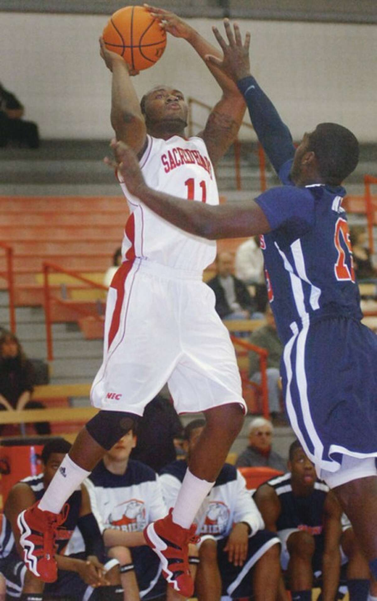 Hour photo/Erik Trautmann Sacred Heart men's basketball player Chris Evans (11) of Stamford is about to let go of a shot against St. Francis (N.Y.) Saturday afternoon at the Pitt Center. Evans scored a career-high 24 points in the Pioneers' 99-84 loss. Norwalk's Evan Kelley, who is a teammate and friend of Evans, didn't play in the game due to an ankle injury.