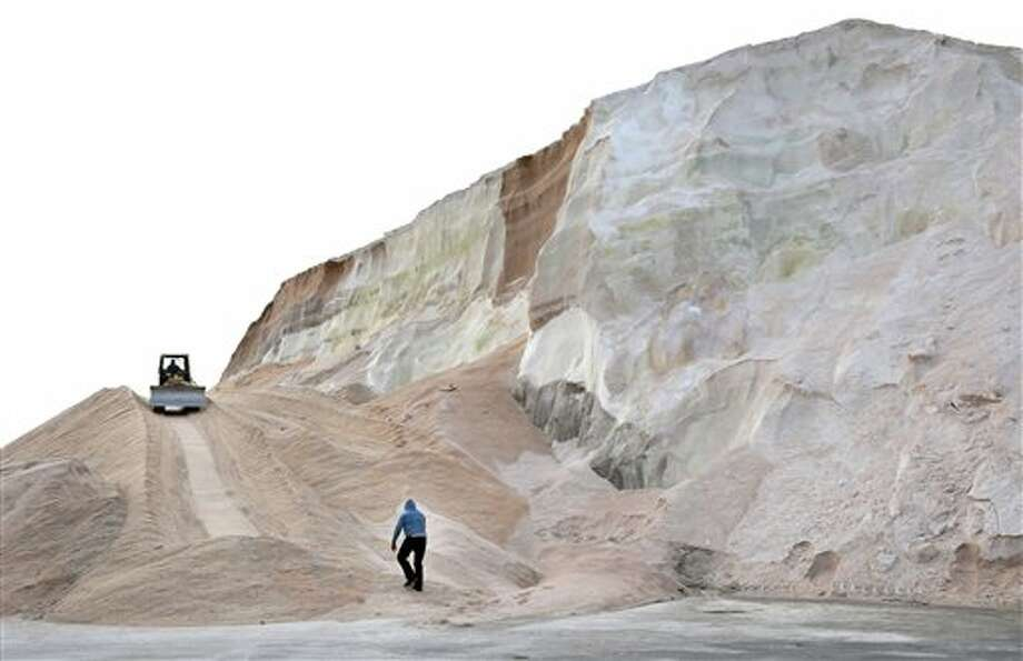 A worker walks up towards a plow smoothing a large salt pile at Eastern Salt Company in Chelsea, Mass., Thursday, Feb. 7, 2013, in preparation for a major winter storm headed toward the U.S. Northeast. The National Weather Service calls for up to 2 feet of snow expected for a Boston-area region that has seen mostly bare ground this winter. (AP Photo/Elise Amendola) / AP
