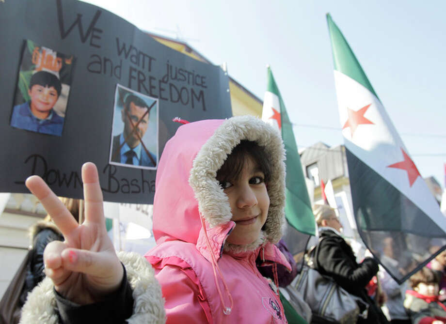 A girl flashes victory sign in front a banner with crossed picture of Syrian President Bashar Assad during a rally against his regime in front of the Syrian embassy in Belgrade, Serbia, Tuesday, March 6, 2012. (AP Photo/Darko Vojinovic) / AP