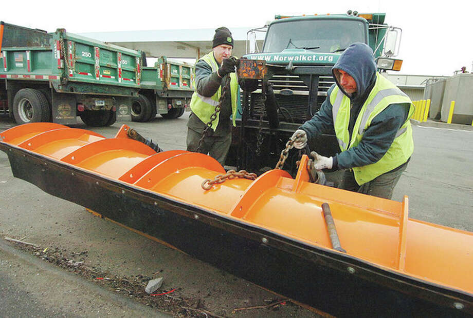 Hour Photo/ Alex von Kleydorff. The city of Norwalk gets ready for a snowstorm as Driver Mike Rosso and Laborer John Tuccinardi attach a plow blade to a City truck at DPW headquaters on Thursday / 2013 The Hour Newspapers