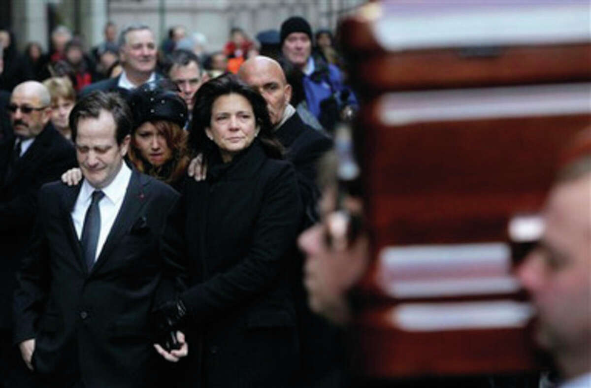 Matthew Badger, left, and Madonna Badger, the parents of three children that were killed in a fire, react as one of the caskets is carried into a church during the funeral in New York, Thursday, Jan. 5, 2012. Hundreds of people streamed into a historic church in the heart of Manhattan on Thursday for the funeral of three young girls who died along with their grandparents during a Christmas morning fire in Stamford, Conn. (AP Photo/Seth Wenig)