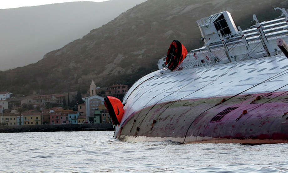 The luxury cruise ship Costa Concordia leans on its side after running aground the tiny Tuscan island of Giglio, Italy, Saturday, Jan. 14, 2012. A luxury cruise ship ran aground off the coast of Tuscany, sending water pouring in through a 160-foot (50-meter) gash in the hull and forcing the evacuation of some 4,200 people from the listing vessel early Saturday, the Italian coast guard said. (AP Photo/Gregorio Borgia) / AP