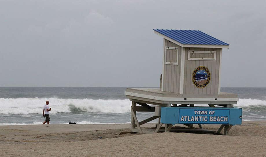 A man walks his dog past a closed lifeguard station in Atlantic Beach, N.C., Friday, Aug. 26, 2011, as Hurricane Irene heads toward the North Carolina coast. (AP Photo/Chuck Burton) / AP