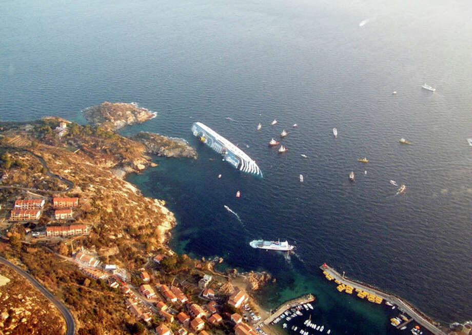 In this photo released by the Guardia di Finanza (border Police), the luxury cruise ship Costa Concordia leans on its side after running aground off the tiny Tuscan island of Giglio, Italy, Saturday, Jan. 14, 2012. The luxury cruise ship ran aground off the coast of Tuscany, sending water pouring in through a 160-foot (50-meter) gash in the hull and forcing the evacuation of some 4,200 people from the listing vessel early Saturday, the Italian coast guard said. The number of dead and injured is not yet confirmed Coast Guard Cmdr. Francesco Paolillo said. (AP Photo/Guardia di Finanza, ho) / Guardia Di Finanza