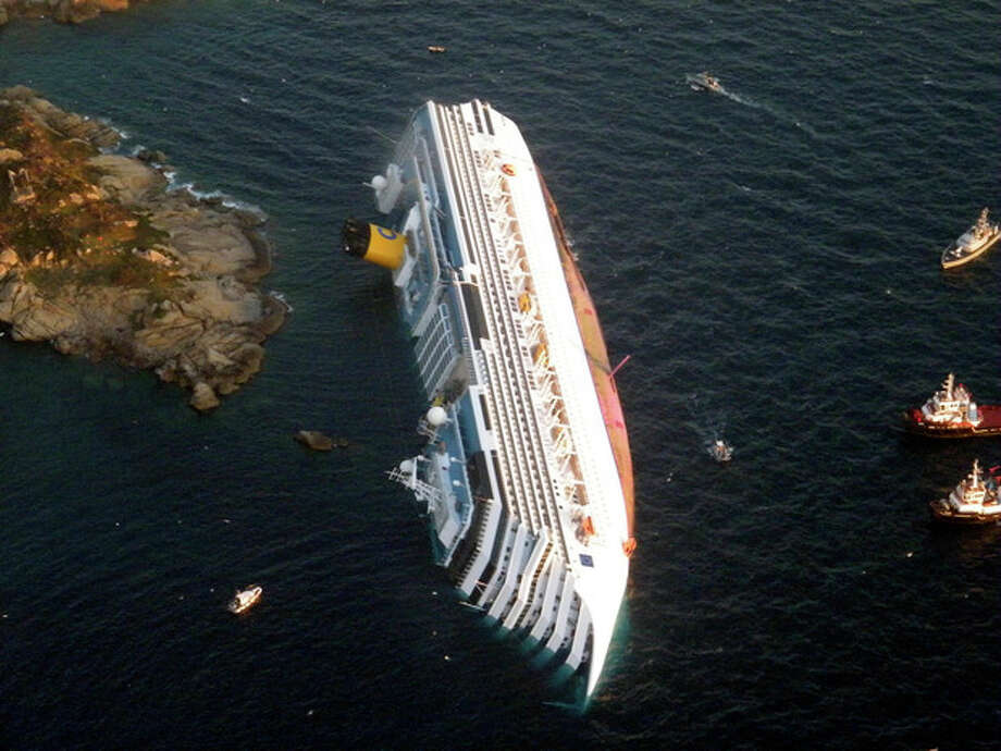 In this photo released by the Guardia di Finanza (border Police), the luxury cruise ship Costa Concordia leans on its side after running aground the tiny Tuscan island of Giglio, Italy, Saturday, Jan. 14, 2012. The luxury cruise ship ran aground off the coast of Tuscany, sending water pouring in through a 160-foot (50-meter) gash in the hull and forcing the evacuation of some 4,200 people from the listing vessel early Saturday, the Italian coast guard said. The number of dead and injured is not yet confirmed Coast Guard Cmdr. Francesco Paolillo said. (AP Photo/Guardia di Finanza, ho) / Guardia Di Finanza