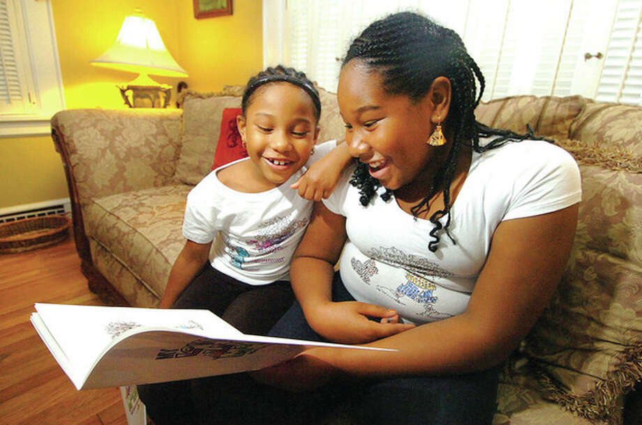 Hour photo / Alex von Kleydorff Six-year-old Samira Lara laughs as she reads the book her older sister, 11-year-old Sahai, wrote about her in ' My Loveable Little Monster.' / ©2012 The Hour Newspapers