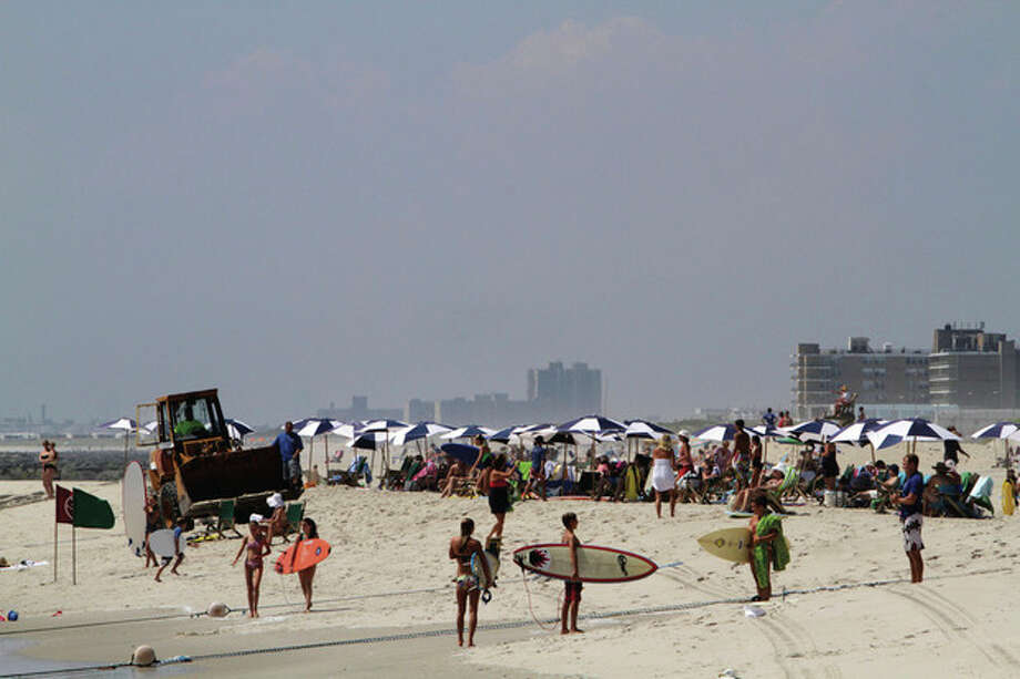 A front loader tractor drives past members of a beach club, Friday, Aug. 26, 2011 in Atlantic Beach, N.Y. Long Island residents in the path of Hurricane Irene girded for wind, rain and flooding as the storm stood poised to bear down on an already saturated New York state. (AP Photo/Mary Altaffer) / AP