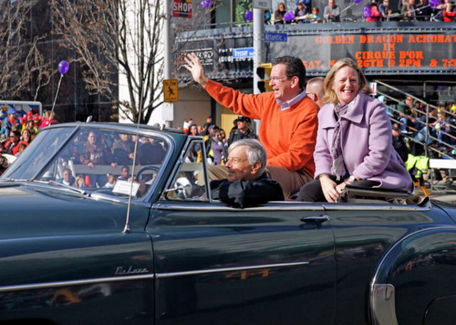 @Cutline:At right: Gov. Dannel P. Malloy waves to the crowd with his wife, Cathy.