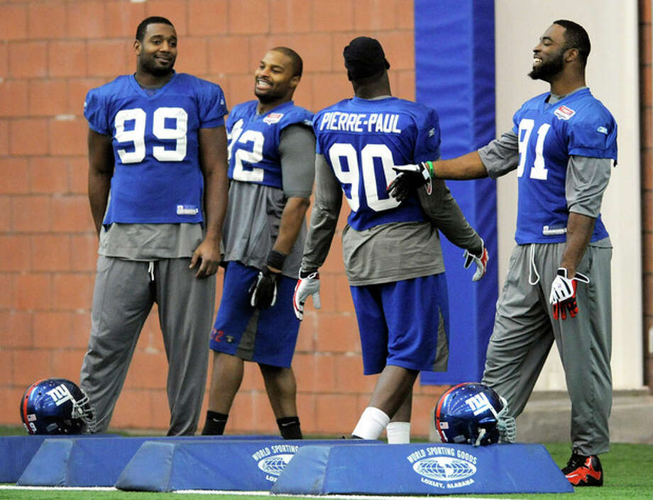 FILE - In this Jan. 19, 2012, file photo, New York Giants' Chris Canty (99), Osi Umenyiora (72), Jason Pierre-Paul (90) and Justin Tuck share a laugh during NFL football practice, Thursday, Jan. 19, 2012, in East Rutherford, N.J. The Giants play the New England Patriots in Super Bowl XLVI on Feb. 5, in Indianapolis. (AP Photo/Bill Kostroun, File) / AP2012