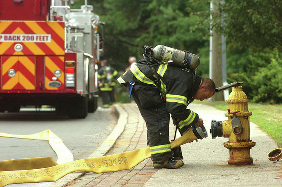 Hour Photo/Alex von Kleydorff. Norwalk Firefighters prepare hoses as they respond to a gas leak on Richards Ave. / 2011 The Hour Newspapers