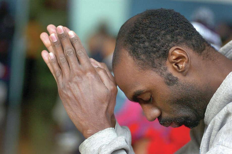 Hour Photo/ Alex von Kleydorff. Ron Minor during prayer at the MLK program in Stamford at the Yerwood Center. / © 2012 The Hour Newspapers