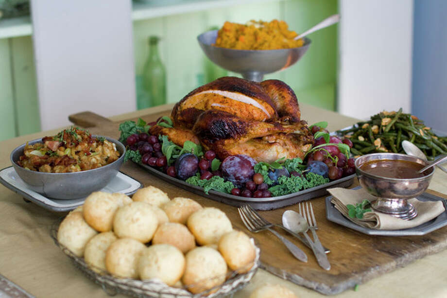 This Oct. 17, 2011 photo shows a sweet and spicy turkey surrounded by, clockwise from top, smashed harvest vegetables, oven-candied green beans amandine, gravy, brown sugar and oatmeal rolls and candied bacon stuffing in Concord, N.H. (AP Photo/Matthew Mead) / FR170582 AP