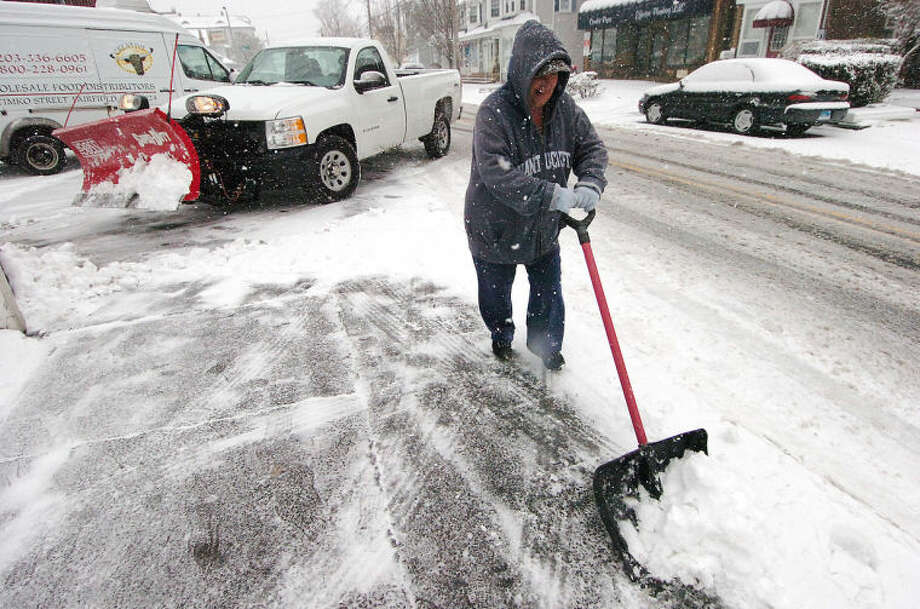 Hour Photo/ Alex von Kleydorff. Gail Smith clears the sidewalk in front of her Norwalk home as a snow plow clears the drive behind her on Friday.