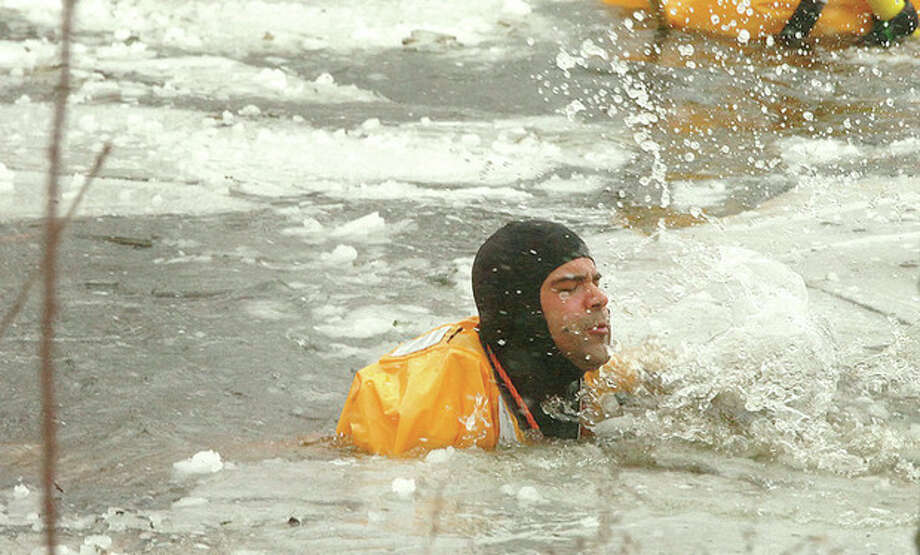 Hour Photo/ Alex von Kleydorff. Norwalk Firefighter Alex Rodriguez with Station 2 Rescue 1 makes his way through the ice to find a Jack Russel terrier that fell through at Flax Hill park on Friday. / 2013 The Hour Newspapers