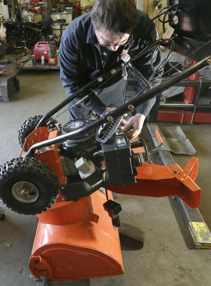Kelly Pomerleau of Andover Small Engine Service repairs a snow blower for a customer in Andover, Mass., Thursday, Feb. 7, 2013, in preparation for a major winter storm headed toward the U.S. Northeast. The National Weather Service calls for up to 2 feet of snow expected for a Boston-area region that has seen mostly bare ground this winter. (AP Photo/Elise Amendola)