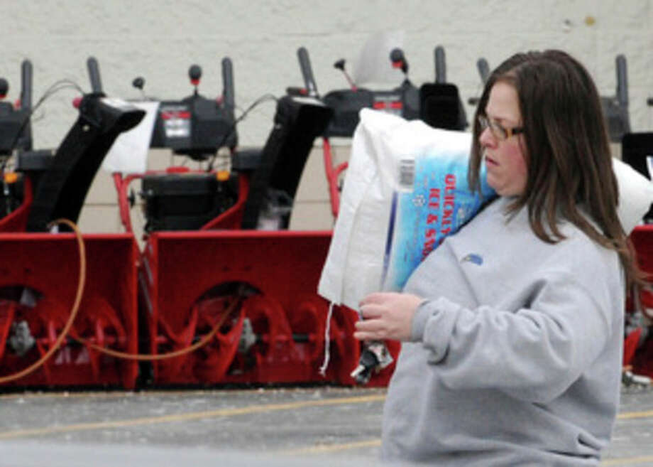 Sue Corsentino walks to her vehicle with a bag of salt in preparation for the coming snow storm Thursday at Lowe's in Greenwich Township, N.J. A winter storm that is heading for New England will be bringing snow, sleet and rain to Pennsylvania along the way. (AP Photo/Express-Times,STEPHEN FLOOD) / Express Times