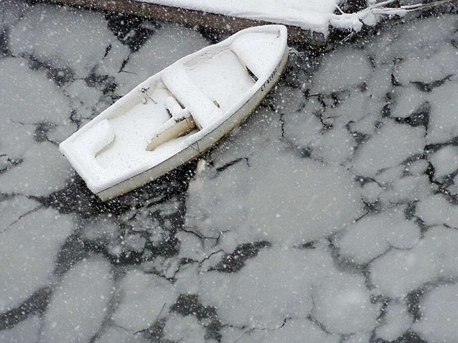 Photo by Chris Bosak Ice forms around a small boat in the Norwalk River on Friday.