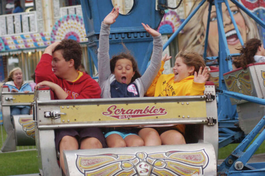 Taylor Lynn, 14, Whitney Lynn, 11, and Lizzie Fernandez ride the Scrambler at at the 32nd annual Oyster Festival in 2010. Hour photo / Erik Trautmann