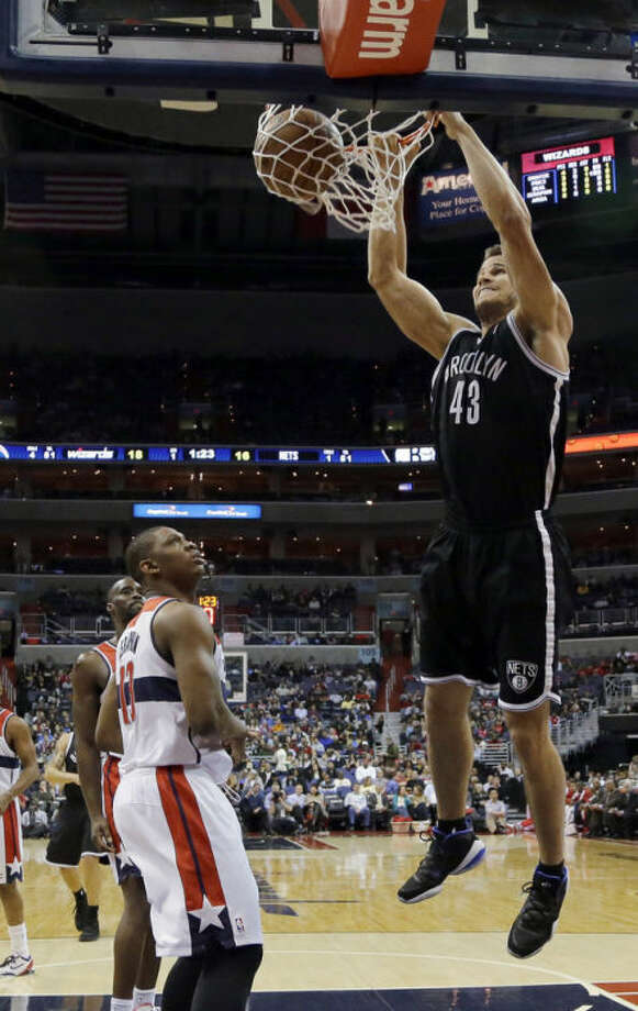 Brooklyn Nets forward Kris Humphries (43) dunks in front of Washington Wizards forward Kevin Seraphin during the first half of an NBA basketball game Friday, Feb. 8, 2013, in Washington. (AP Photo/Alex Brandon)