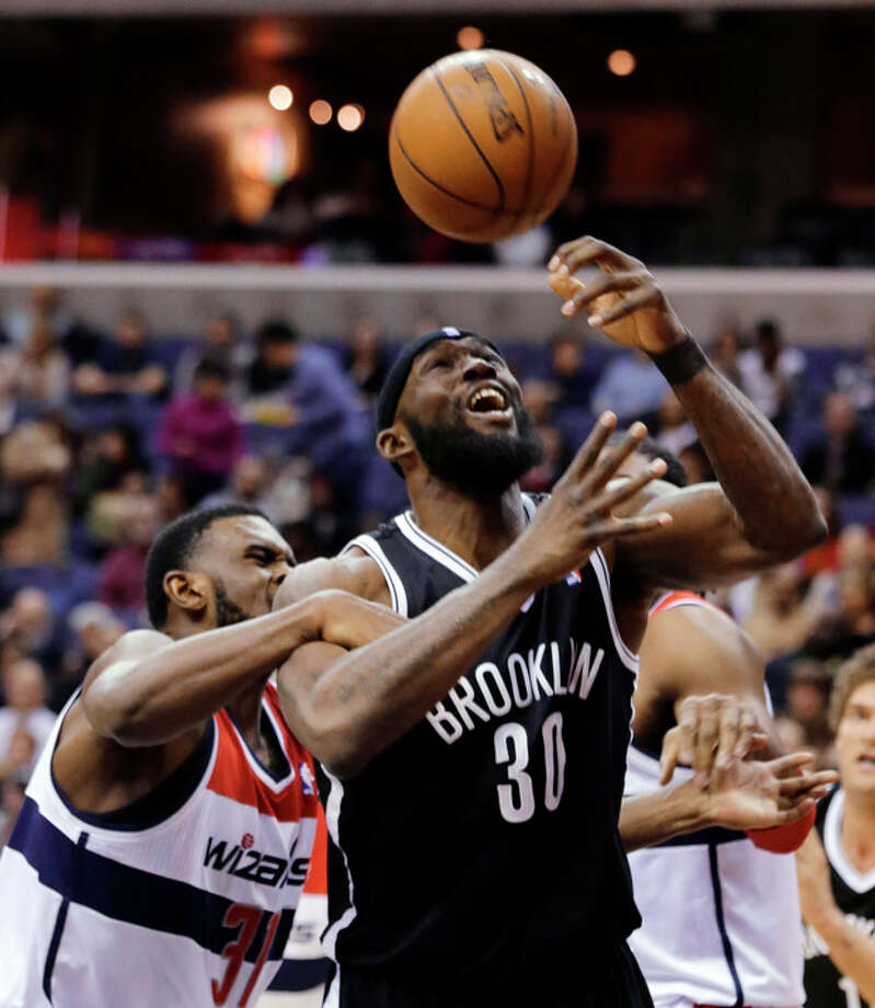 Washington Wizards forward Chris Singleton (31) grabs the arm of Brooklyn Nets forward Reggie Evans (30) as Evans tries to shoot during the first half of an NBA basketball game Friday, Feb. 8, 2013, in Washington. (AP Photo/Alex Brandon) / AP