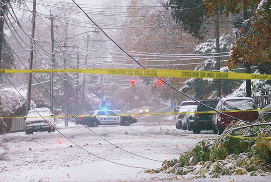 Hour photo / Erik Trautmann Downed wires caused by tree limbs weighed down with slushy snow during a storm Saturday cause officials to close East Avenue in Norwalk. Thousands of Norwalkers were without power as the storm hit the area. / (C)2011, The Hour Newspapers, all rights reserved